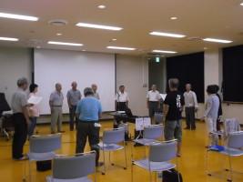 相撲甚句体験講座で、十数名の参加者が輪になって相撲甚句を習っている様子。